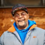 smiling older black man in glasses and baseball cap