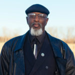 confidently smiling goateed black man with cap and glasses