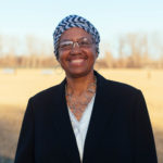 grinning black woman with glasses standing outside