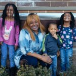 Grinning black woman with long red hair kneeling with three smiling children