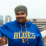 Grinning black woman wearing knit cap and St. Louis Blues hoodie