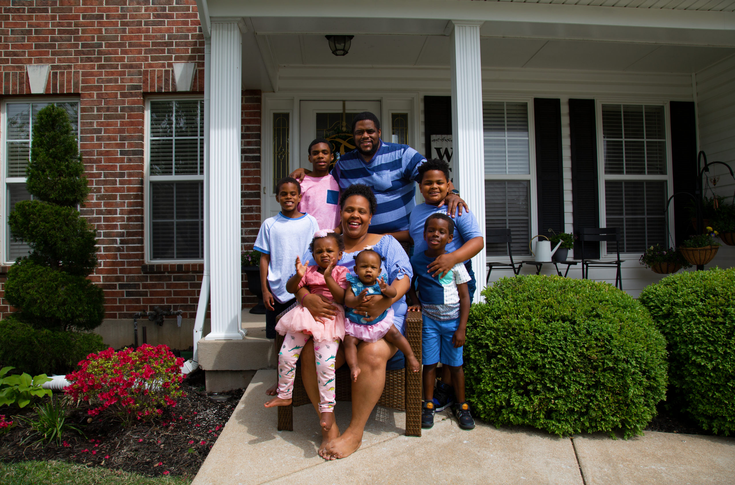 Smiling Black family in front of their home